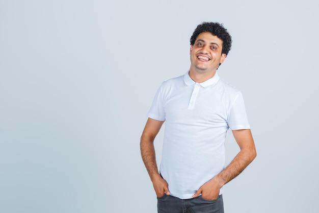 Junger mann posiert beim stehen im weißen t-shirt, in der hose und sieht fröhlich aus, vorderansicht.