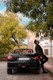 Junger mann posiert in einem cabrio.