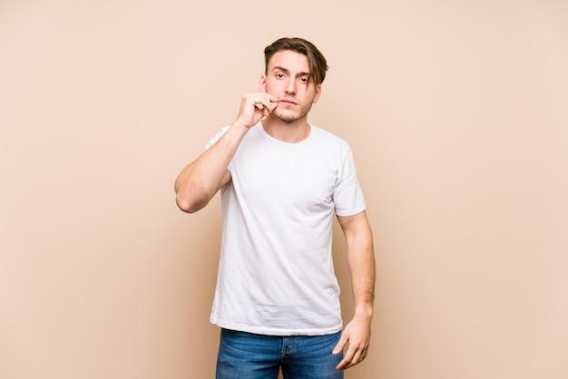 Junger mann posiert mit den fingern auf den lippen, die ein geheimnis halten