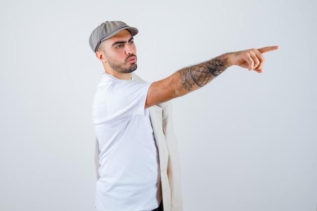 Junger mann posiert vorne mit jacke auf der schulter und zeigt nach rechts in weißem t-shirt, jacke und grauer mütze und sieht ernst aus