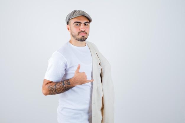 Junger mann posiert vorne mit jacke auf der schulter und zeigt ruf mich geste in weißem t-shirt, jacke und grauer mütze und sieht ernst aus