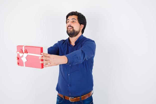 Junger mann präsentiert geschenkbox in blauem hemd und jeans und sieht ernst aus, vorderansicht.