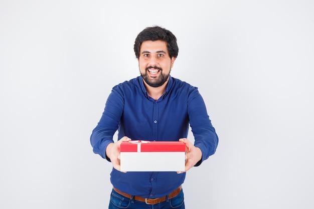 Junger mann präsentiert geschenkbox mit beiden händen in blauem hemd und jeans und sieht optimistisch aus. vorderansicht.