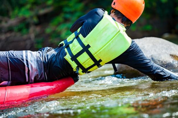 Junger mann raftet auf dem fluss. extremer und spaßiger sport