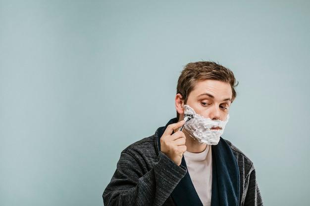 Junger mann rasiert sich den bart