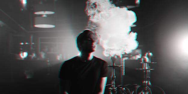 Junger mann raucht eine wasserpfeife und stößt eine rauchwolke aus