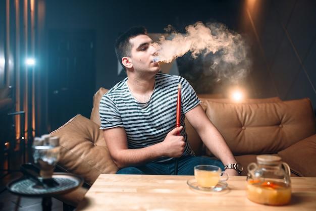 Junger mann raucht und entspannung an der shisha-bar. tabakrauch, nachtlebensstil