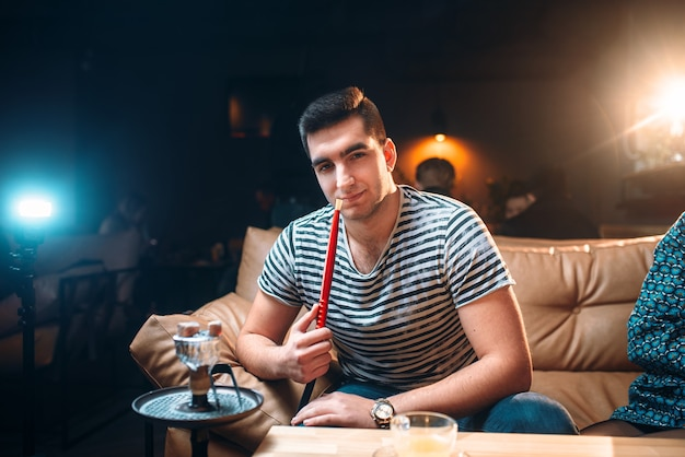 Junger mann raucht und entspannung an der shisha-bar