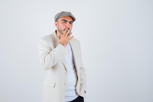 Junger mann raucht zigaretten, während er die hände an der taille in weißem t-shirt, jacke und grauer mütze hält und ernst aussieht