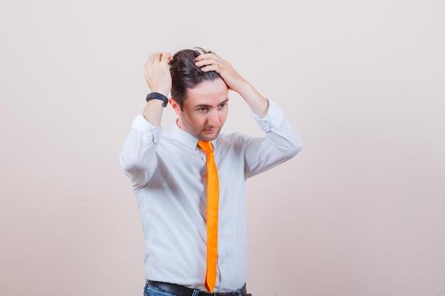 Junger mann reibt sich den kopf, während er in hemd, krawatte, jeans denkt und gut aussieht