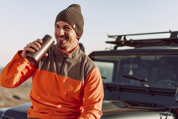 Junger mann reisender, der von seinem thermocup trinkt, während auf einer wanderung, nahaufnahmeporträt angehalten wird