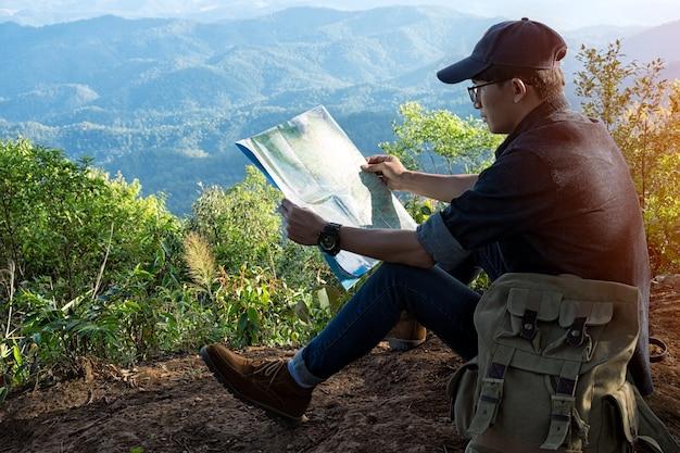 Junger mann-reisender mit dem kartenrucksack, der mit felsigen bergen im freien auf sommerferien und -lebensstil wandern im freien sich entspannt, die wandern