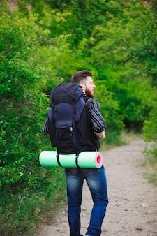 Junger mann reisender mit rucksack entspannend im freien. sommerferien und lifestyle-wanderkonzept.
