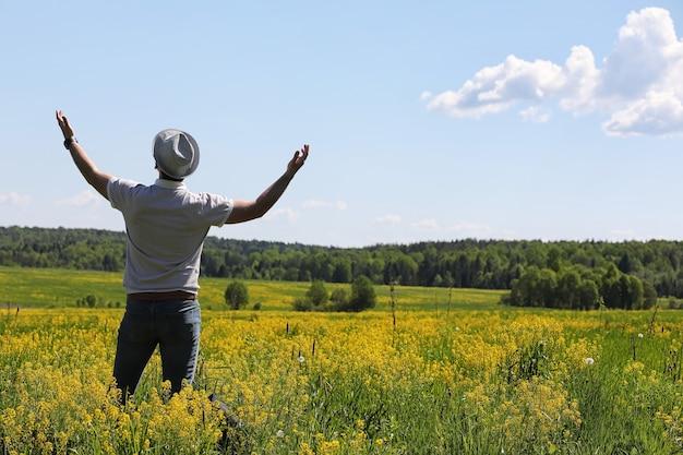 Junger mann reist mit einem rucksack an einem sommertag im freien