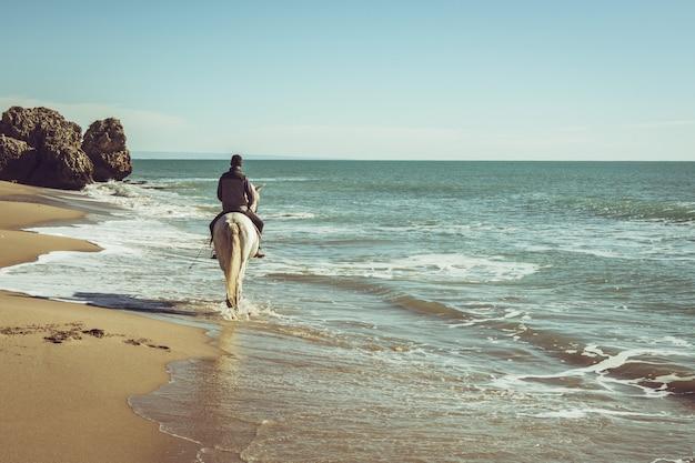 Junger mann reiten ein weißes pferd am strand
