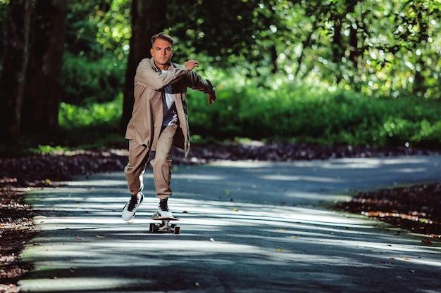 Junger mann reitet ein skateboard im park