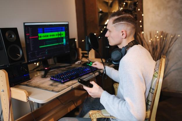 Junger mann ruft freund an, damit er musik hört, die er selbst isolierten mann zu hause aufnimmt