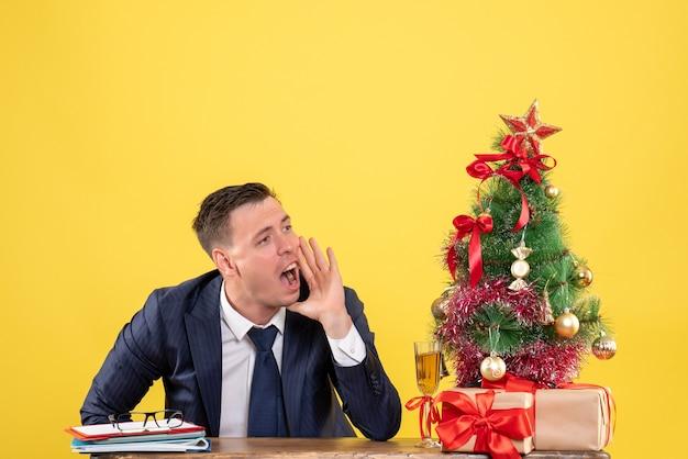 Junger mann ruft jemanden an, der am tisch in der nähe von weihnachtsbaum und geschenken auf gelb sitzt Kostenlose Fotos