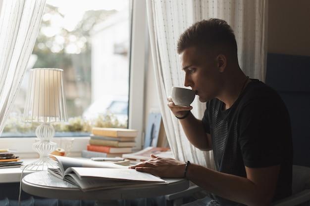 Junger mann ruht in einem restaurant, liest ein buch und trinkt kaffee.