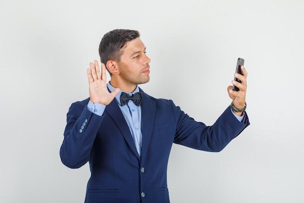 Junger mann sagt hallo auf videoanruf im anzug