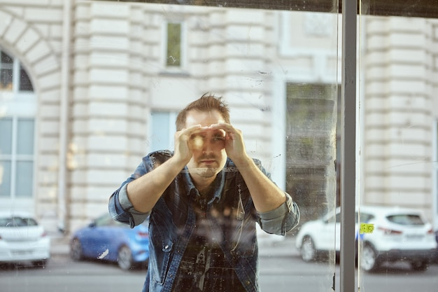 Junger mann schaut durch glas der öffentlichen verkehrsstation.