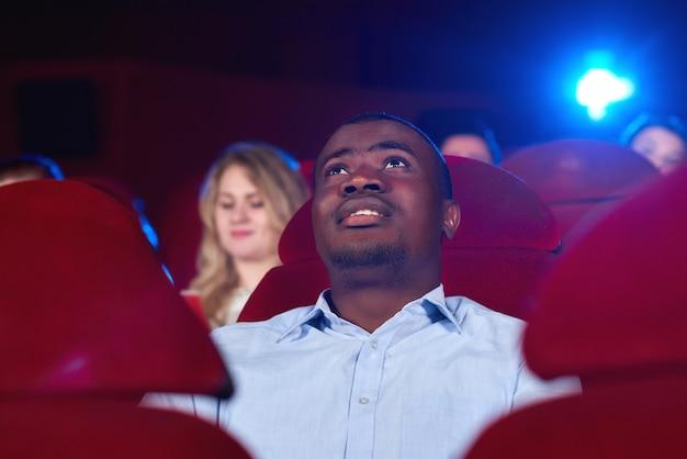 Junger mann schaut sich im kino einen film an
