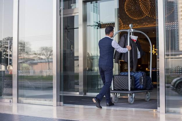 Junger mann schiebt gepäckwagen mit koffertaschen und rucksäcken zum eingang
