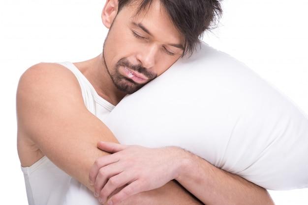 Junger mann schläft mit dem kopf, der auf kissen stillsteht.