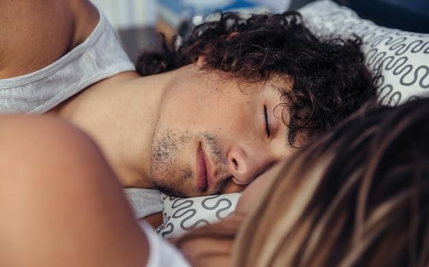 Junger mann schläft mit seinem partner im bett