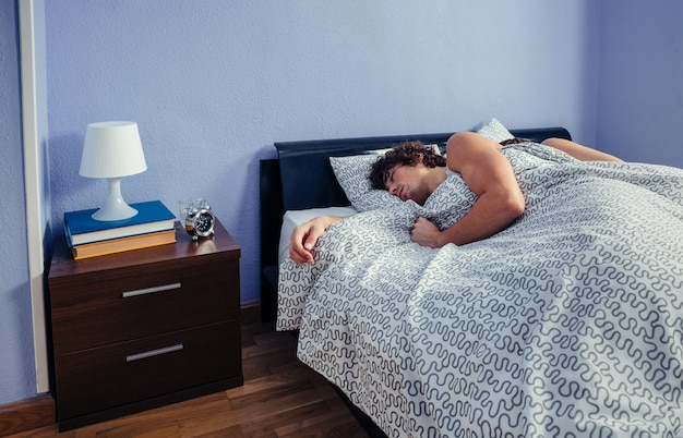 Junger mann schläft mit seiner frau auf dem rücken im bett