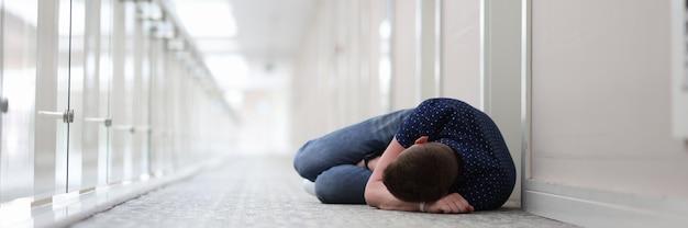 Junger mann schläft unter der tür des hotelkomplexes