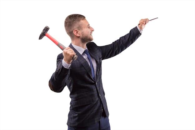 Junger mann schlägt mit einem lächeln hammer auf den meißel