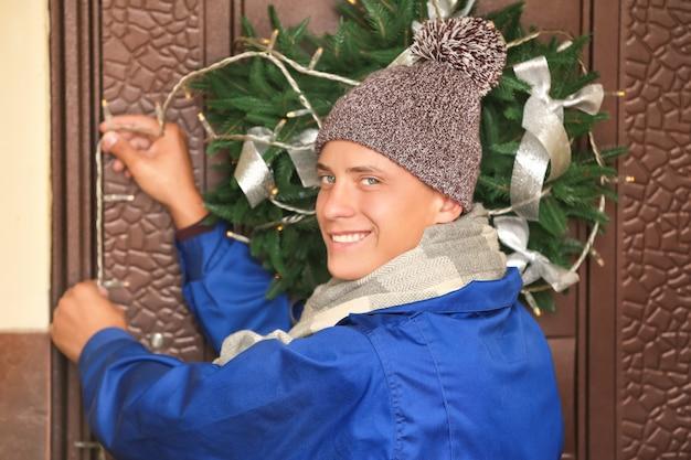 Junger mann schmückt weihnachtskranz mit lichtern an der tür des hauses
