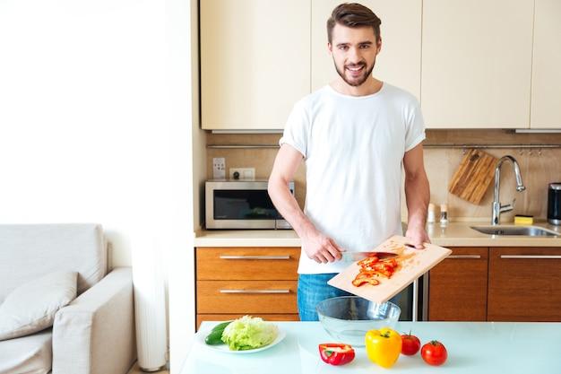 Junger mann schneidet gemüse in der küche