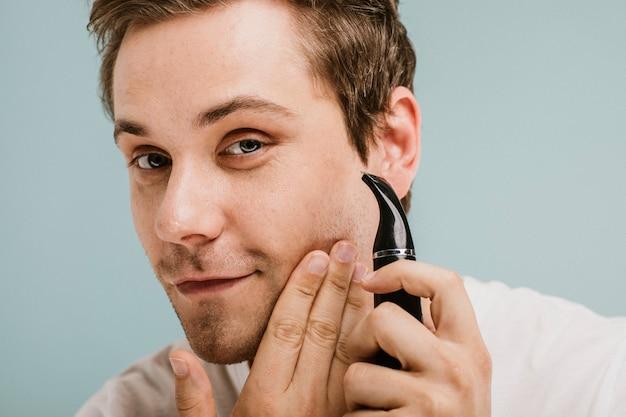 Junger mann schneidet seinen bart