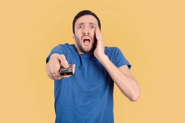 Junger mann schockiert vor dem fernseher.