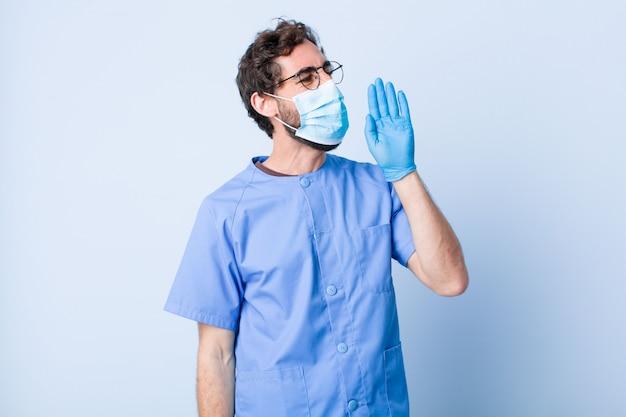 Junger mann schreit laut und wütend, um platz auf der seite zu kopieren, mit der hand neben dem mund. coronavirus-konzept