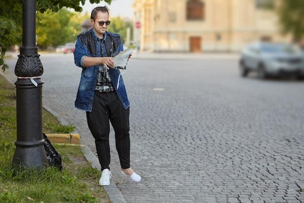 Junger mann schüttelt stein aus seinen sportschuhen, während er in der europäischen stadt steht.