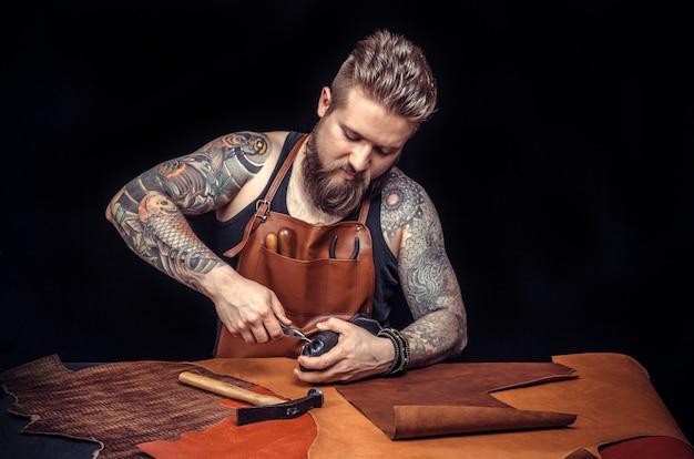 Junger mann, schuhmacher, repariert alten handgefertigten schuh in seiner werkstatt und schaut in die kamera