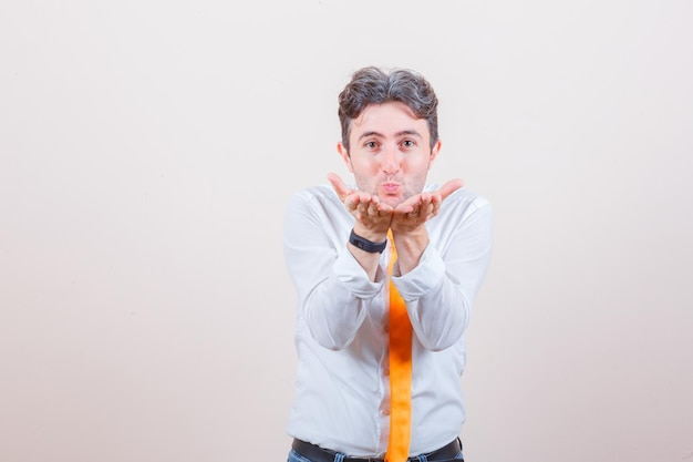 Junger mann sendet luftkuss mit geschmollenen lippen im weißen hemd