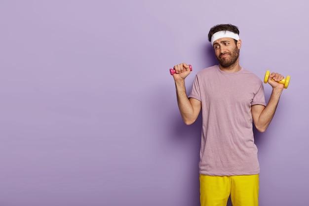 Junger mann sieht unfreiwillig aus, hält hanteln in beiden händen