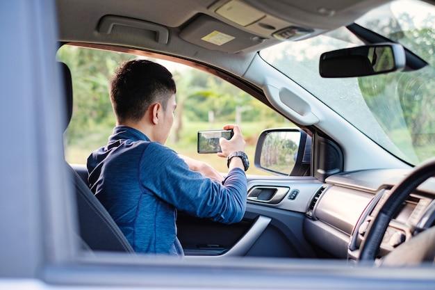 Junger mann sitzen innerhalb des autos, das photohraphy mit smartphone nimmt. smartphone fotografieren.
