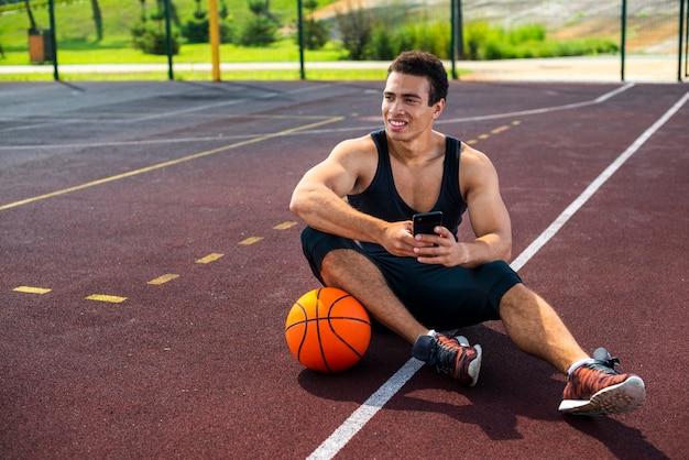 Junger mann sitzt auf dem basketballplatz