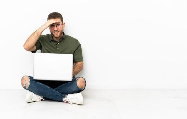 Junger mann sitzt auf dem boden und schaut mit der hand weit weg, um etwas zu suchen