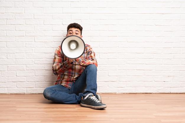 Junger mann sitzt auf dem boden und schreit durch ein megaphon