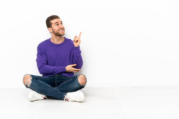 Junger mann sitzt auf dem boden und zeigt eine tolle idee great