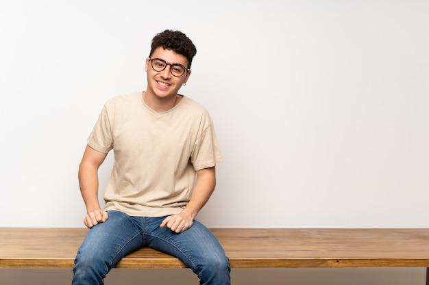 Junger mann sitzt auf dem tisch mit brille und glücklich