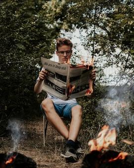 Junger mann sitzt auf einem stuhl, der eine brennende zeitung hält und liest