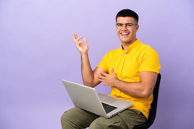 Junger mann sitzt auf einem stuhl mit laptop, der die hände zur seite ausstreckt, um einzuladen, zu kommen