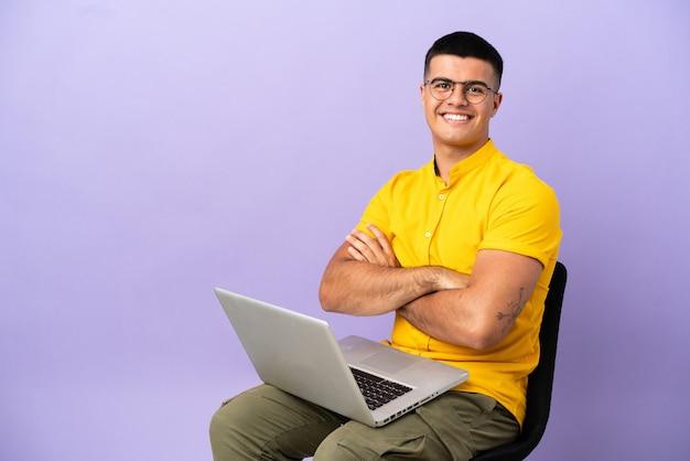 Junger mann sitzt auf einem stuhl mit laptop mit verschränkten armen und freut sich